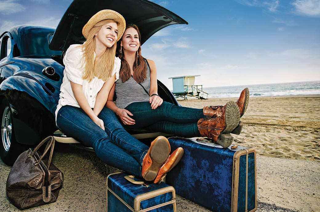 Two-girls-sitting-on-the-boot-of-a-car